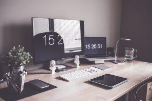 na zdj.: dwa ekrany na biurku